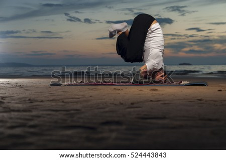 Young flexible man with tattoos doing high level yoga on the beach at sunset. head stand exercise.