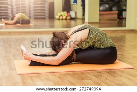Young flexible woman in a yoga stretching head to knee pose - stock photo