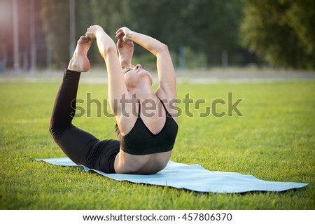 Young flexible woman in black sportswear exercising yoga outdoors. Bow Pose.