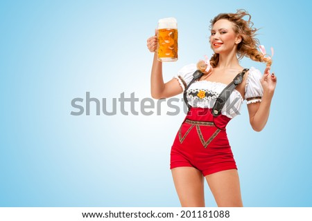 Young flirting sexy Swiss woman wearing red jumper shorts with suspenders in a form of a traditional dirndl, holding a beer mug on blue background. - stock photo