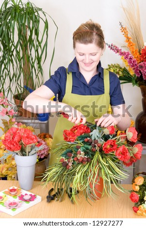 Young florist cutting flowers and working on an arrangement - stock photo
