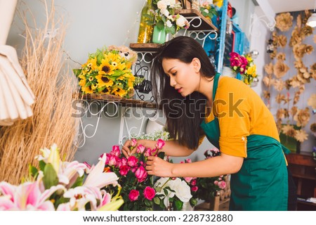 Young florist examining flowers at the shop - stock photo