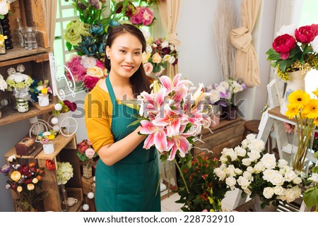 Young florist working at flower shop - stock photo