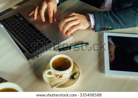 Young focused businessman sitting in cafe and working on his laptop. On the table tablet pc and coffee. Close up - stock photo
