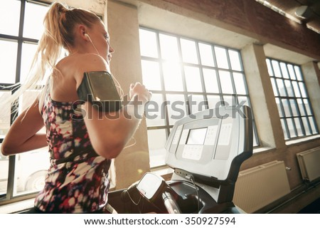 Young focused female working out at gym jogging on a treadmill. Fitness woman doing running exercise in the health club. - stock photo