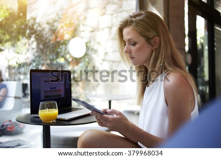 Young focused woman reading news on mobile phone while sitting with open net-book in cafe, female freelancer watching video on cell telephone during break after creating website on laptop computer - stock photo