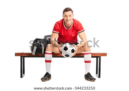 Young football player holding a ball and sitting on a wooden bench isolated on white background - stock photo