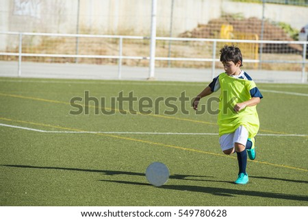 Young football player in a training at the field