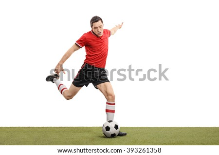 Young football player kicking a ball and playing football on a grass field isolated on white background - stock photo