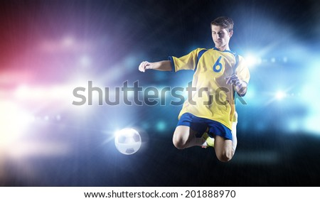 Young football player on stadium kicking ball