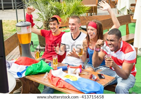 Young football supporter fans cheering with beer watching soccer match on tv - Friends people with multicolored t shirts and flags having fun - Sport championship concept - Warm afternoon color tones - stock photo