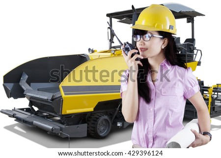 Young forewoman talking on the radio transmitter while holding a blueprint with spreader machine asphalt on the background - stock photo