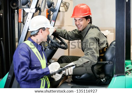 Young forklift driver communicating with supervisor at warehouse