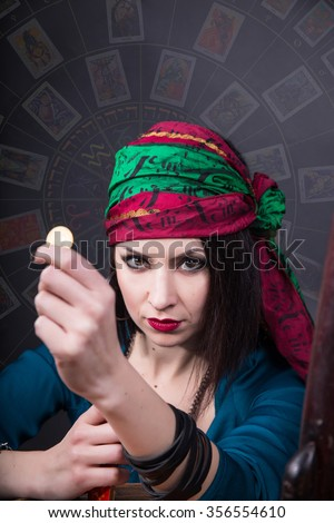 Young fortune teller with a penetrating gaze reaches out to the coin forward. Predicting the future. - stock photo