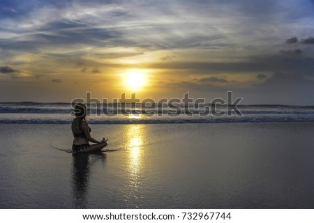 young free woman sitting looking to sea sunset horizon with beautiful sun practicing yoga and meditation at beautiful Asian beach in tourism vacation and summer holiday trip fun