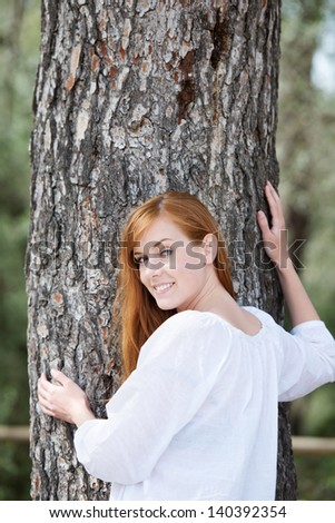 Young fresh woman posing over the tree trunk background - stock photo