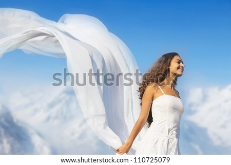 Young fresh woman with flying fabric on top of the mountains