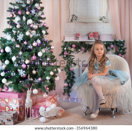 Young friendly girl seat near gift box and dressed Christmas tree. New Year celebration. - stock photo