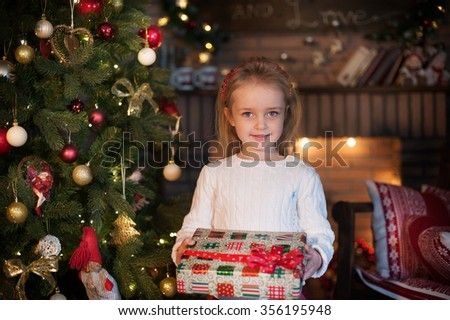 Young friendly girl smile and hold gift box near Christmas tree. New Year celebration. - stock photo