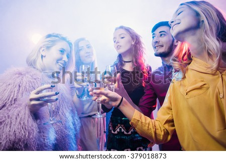 Young friendly people toasting in night club
