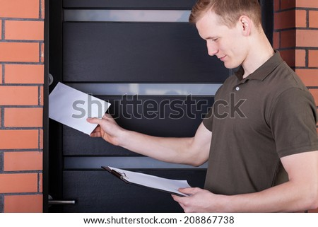 Young friendly postman giving person the letter