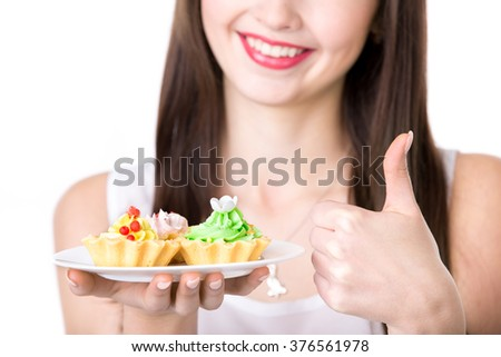 Young friendly smiling woman holding in her hand plate with delicious cream tart cakes, showing thumbs up, studio, white background, isolated, close-up - stock photo