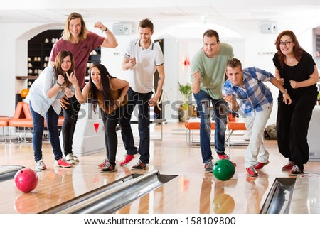 Young friends bowling while people cheering in club - stock photo