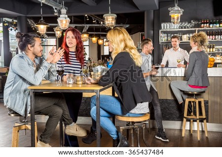 Young friends conversing while sitting at table in bar - stock photo