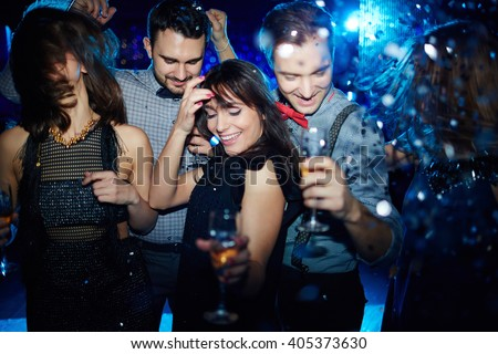 Young friends dancing energetically in nightclub - stock photo