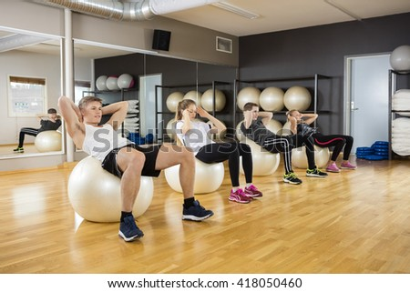 Young Friends Doing Crunches On Ball In Gym