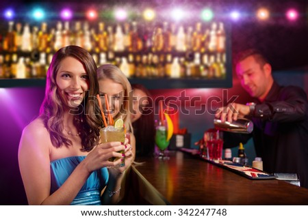 Young friends drinking cocktails together at night bar party - stock photo