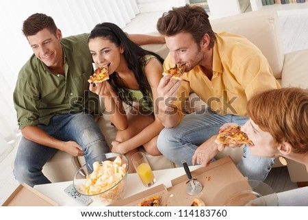 Young friends eating pizza at home, having fun. - stock photo