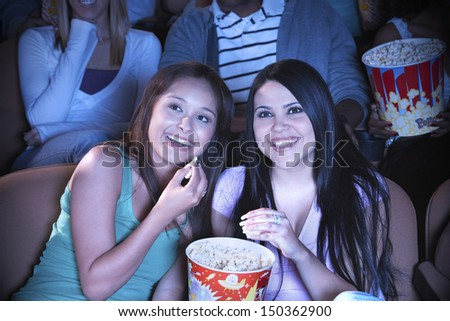 Young friends eating popcorn while watching film in movie theater