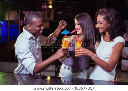 Young friends enjoying while having cocktail drinks at bar counter in bar