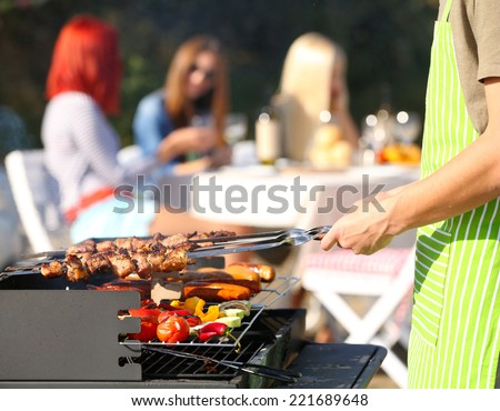 Young friends having barbecue party, outdoors