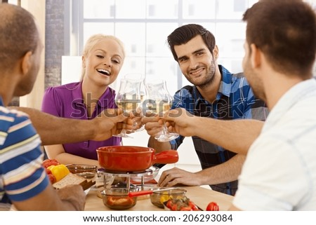 Young friends having dinner together, clinking glasses, smiling, having fun. - stock photo