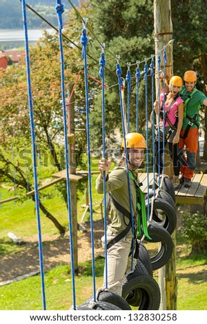 Young friends having fun in adventure park in helmets - stock photo