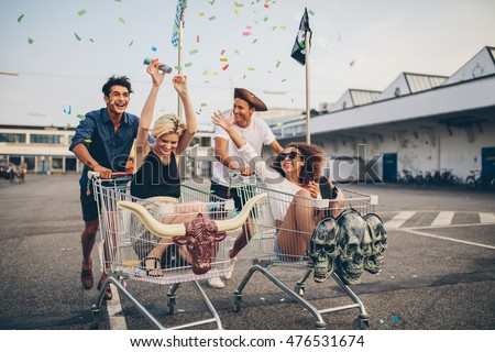 Young friends having fun on shopping trolleys. Multiethnic young people racing on shopping cart.