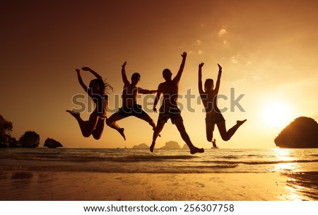 Young friends having fun on the beach and jumping against a backdrop of a sunset over the sea - stock photo