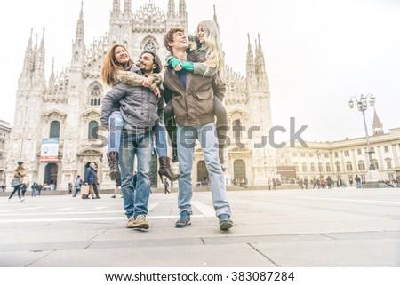 Young friends having fun outdoors - Five students outdoors, men carrying two girls on piggyback - Cheerful young people sightseeing a city, Duomo cathedral in the background - stock photo