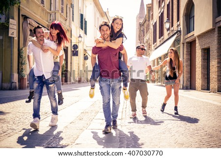 Young friends having fun outdoors - Six students outdoors, men carrying two girls on piggyback - stock photo