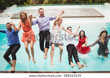 Young friends holding hands and jumping in the swimming pool - stock photo