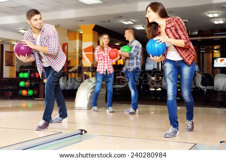 Young friends playing in bowling alley - stock photo