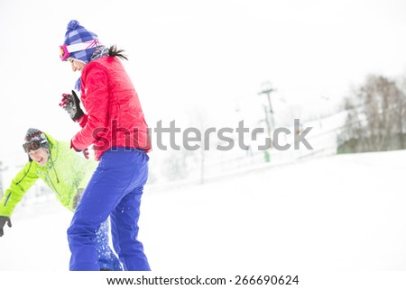 Young friends playing in snow - stock photo