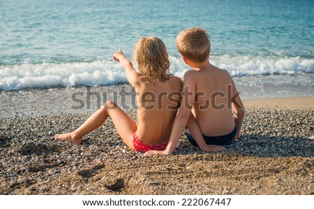 Young friends portrait at the beach looking at the sea. Children at the seaside.