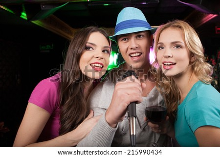 Young friends singing into microphone at party. man and woman holding close and singing - stock photo