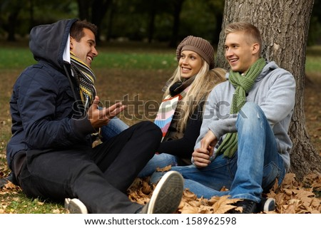 Young friends sitting on ground among leaves in autumn park, talking, smiling. - stock photo