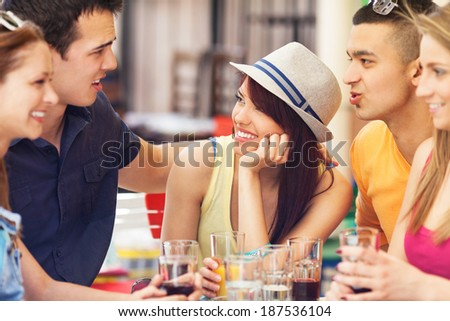 Young friends sitting on table in cafe - stock photo