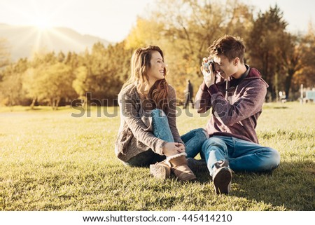 Young friends sitting on the grass, he is taking a picture of his girlfriend using a digital camera, natural landscape on background