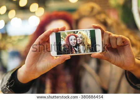 Young friends taking a selfie with cellphone in a restaurant bar